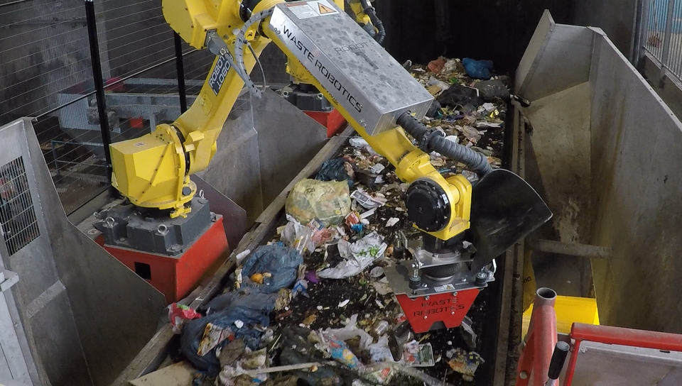 A robot sorts through a stream of waste on a conveyor belt.